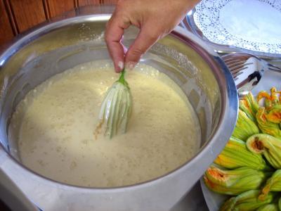Plonger les fleurs de courgettes dans la pâte à frire